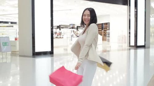 Woman Walking at the Mall and Carrying Shopping Bags