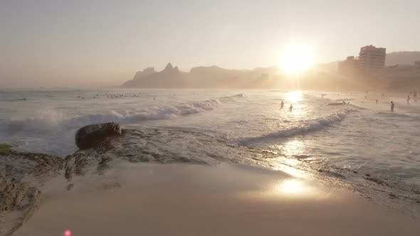 Thumbnail for Slow motion, sunset shot of white waves rolling onto beach as people swim