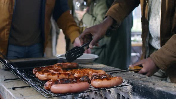 Thumbnail for Men Serving Grilled Sausages on Plate