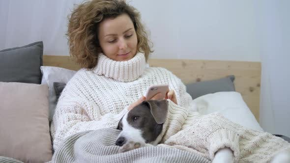 Thumbnail for Young Woman In Knit Sweater Smiling And Using Smartphone In Bed With Dog