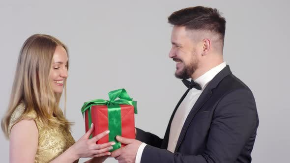 Cover Image for Man in Suit Giving Present to Happy Woman
