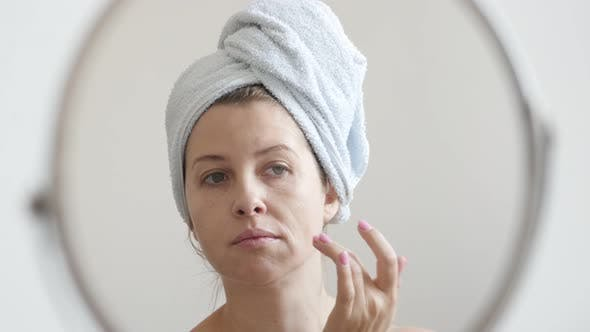 Thumbnail for Female in front of make-up mirror with towel on head 4K 2160p 30fps UltraHD footage - Woman applying