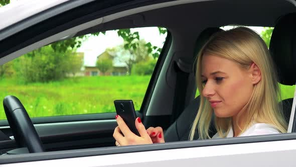 Young Attractive Blond Woman Sits in the Car and Works on the Smartphone