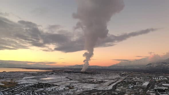 Thumbnail for Aerial winter sunset view flying backwards viewing smoke from factory