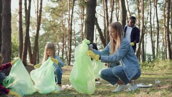 Thumbnail for Multiracial Adults Together with Children Collecting Garbage Into Plastic Bags from Park Territory