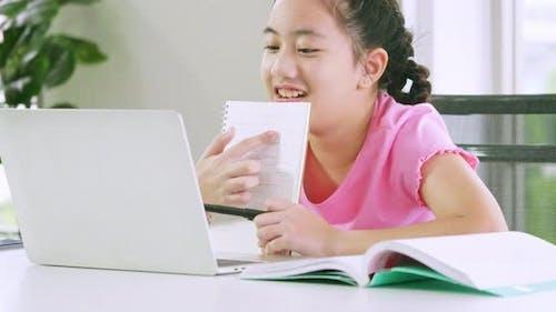 Ein Mädchen macht ihre Schularbeit mit Laptop. Fernunterricht und Online-Bildungskonzept.