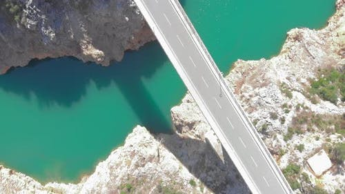 Aerial top view of tranquil calm river with clear azure water and mountain cliffs