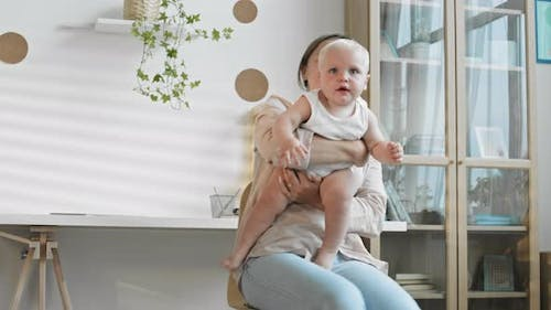 Woman Holding Baby while Sitting on Office Chair