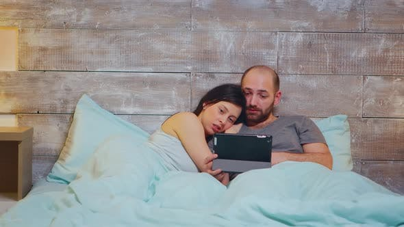 Caucasian Couple in Pajamas Lying in Bed