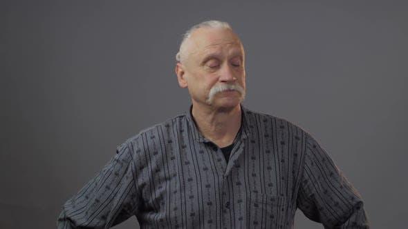 Thumbnail for Arrogant Senior Grey Haired Man in Dark Shirt Looks Down