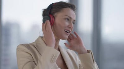 Positive Slim Beautiful Woman in Headphones Enjoying Music Dancing at Window