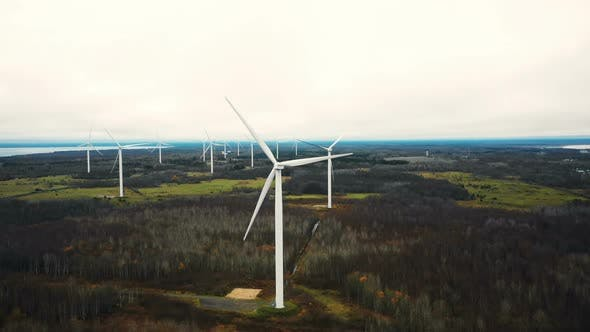 Thumbnail for Amazing Aerial Panoramic View of Windmill Turbine Farm Generating Power in Autumn Forest Lake Field