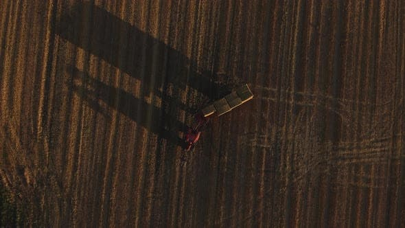 Aerial Shot of Forklift Truck in a Farming Field Collecting Haystacks