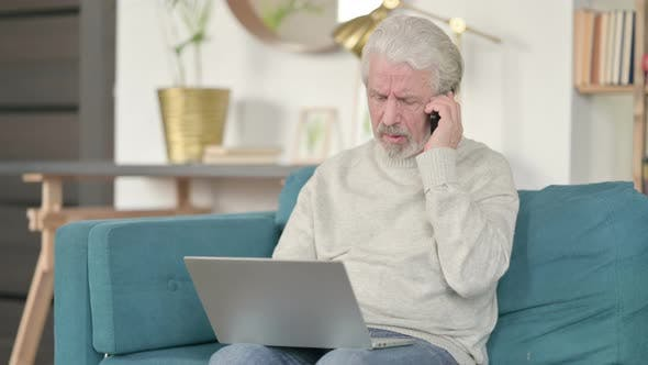 Cover Image for Old Man with Laptop Talking on Smartphone on Sofa