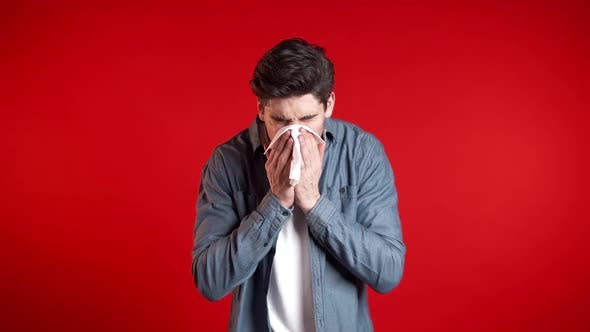 Thumbnail for Young Man Sneezes Into Tissue. Isolated Guy on Red Studio Background Is Sick