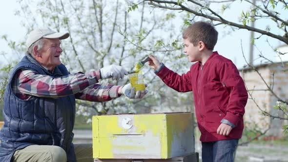 Friendly Family, a Joyful Boy Together with His Elderly Grandfather Restore Old Beehive with a Brush