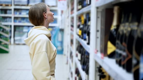 Thumbnail for Girl Choosing Champagne at Supermarket. Cheerful Woman Holding Champagne Bottle While Standing in