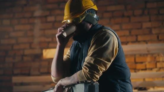 Mann trinkt Heißgetränk auf Baustelle