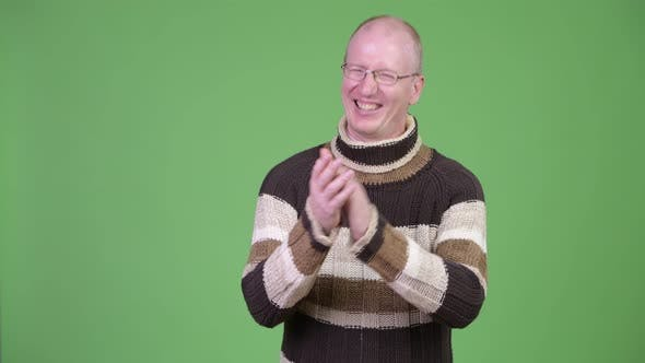 Thumbnail for Happy Mature Bald Man with Turtleneck Sweater Clapping Hands While Thinking