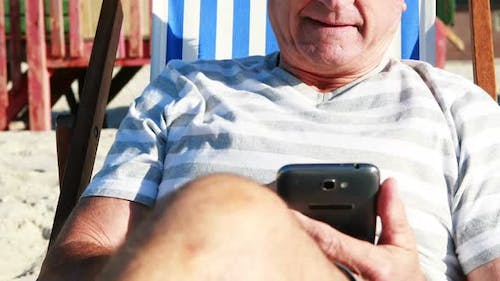 Senior man talking on mobile phone while relaxing on sunlounger
