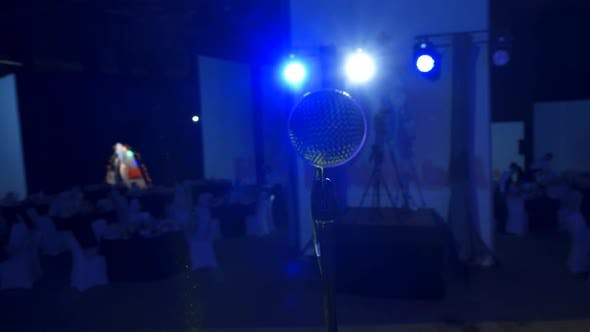 Vocal Microphone with Stand on Big Stage in Hall of Auditorium or Atrium with Blue Soffit at the