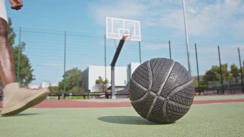 Close Up Shot of Black Guy Taking Basketball Ball and Dribbling It To Hoop