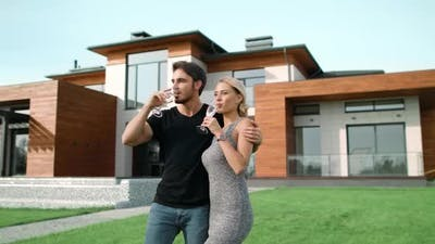 Happy Couple Drinking Champagne with Near Luxury Home Together