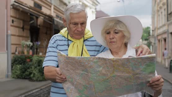 Thumbnail for Senior Male and Female Tourists Standing with a Map in Hands Looking for Route