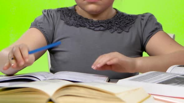 Cover Image for Girl Leafing Through a Book and Writing in a Notebook. Green Screen. Close Up