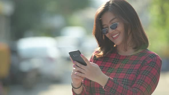 Thumbnail for Happy Young Beautiful Asian Businesswoman Using Phone Outdoors