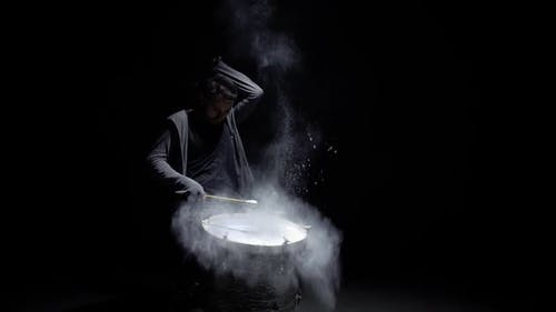 Portrait of a Drummer in Profile on a Black Background
