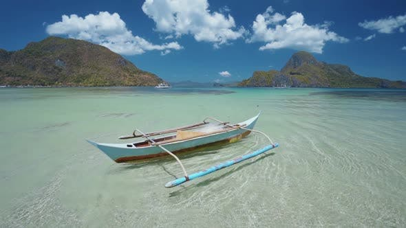 Thumbnail for Lonely Fishing Boat in Slowmo Floating in Open Blue Lagoon of El Nido Bay, Palawan, Philippines
