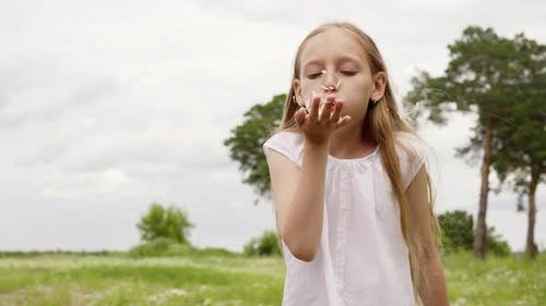 Cute Teenager Girl Blowing Daisy Petals From Palm Hand to Camera