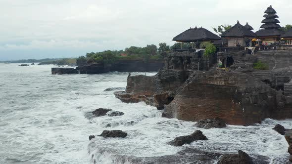 Low Aerial View of Strong Ocean Waves Crashing Into Dark Rocky Cliff with Tanah Lot Temple in Bali