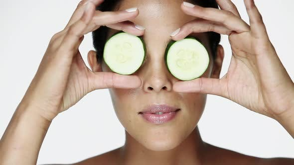 Woman holding cucumber slices over her eyes