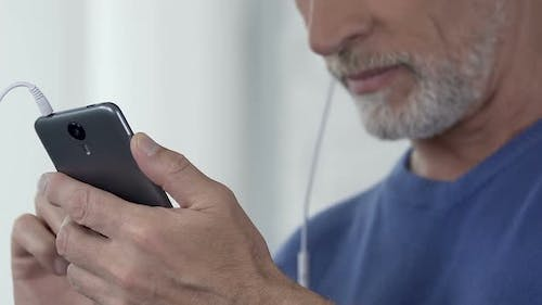 Man Composing Playlist of His Favorite Songs on Smartphone, Accessible App