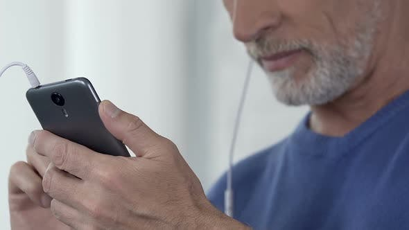 Cover Image for Man Composing Playlist of His Favorite Songs on Smartphone, Accessible App