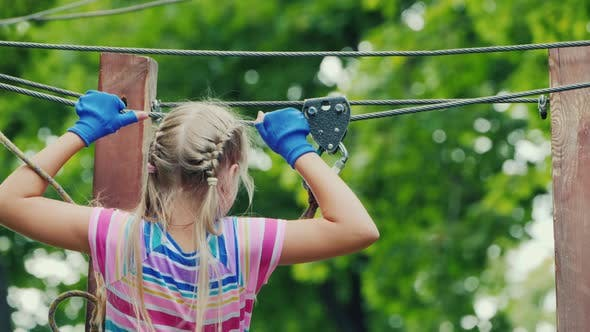 Thumbnail for Back View of A Brave Girl Moves Along the Ropes Between the Trees, Uses a Safety Rope