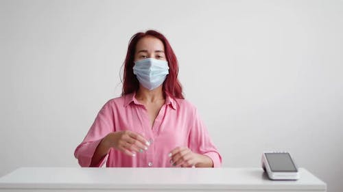 Woman Administrator in Medical Mask Stands Behind Reception and Invites Clients