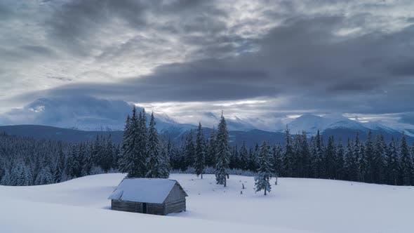 Zeitraffer fließender Wolken über Berge und Wald im Winter