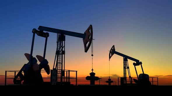 Two Oil Pump Jacks Extracting Crude Oil Under Beautiful Sunset Sky