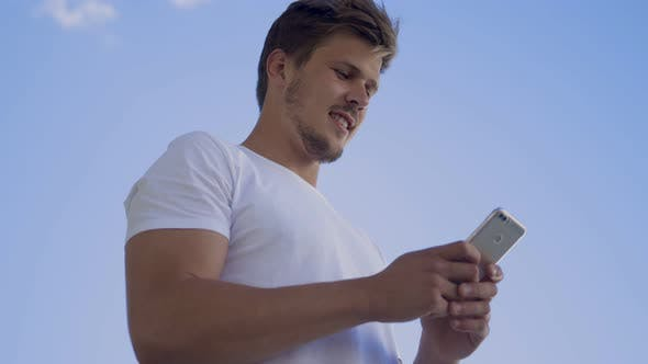 Cover Image for Smiling Young Guy Messaging on Smartphone Outdoor