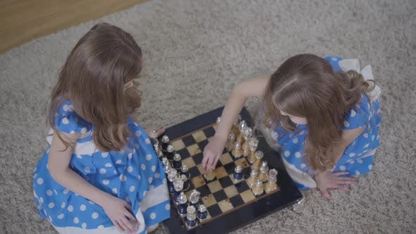 Thumbnail for Top View of Two Brunette Caucasian Twin Sisters Playing Chess Indoors. Little Girls in Elegant Blue