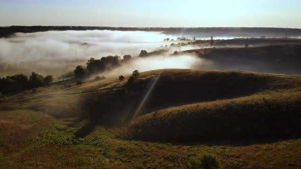 Thumbnail for Drone Flies Into the Fog Over Rolling Hills