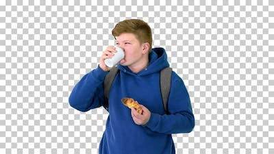 Schoolboy having a croissant and drinking, Alpha Channel
