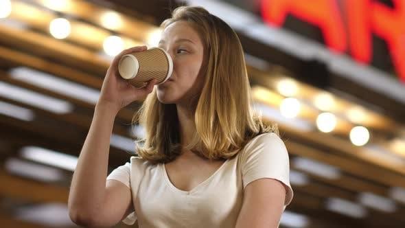 Thumbnail for junge attraktive Frau mit einem To Go Tasse Kaffee