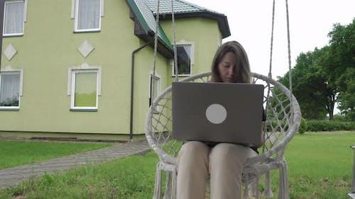 Woman in Garden Chair Using Laptop