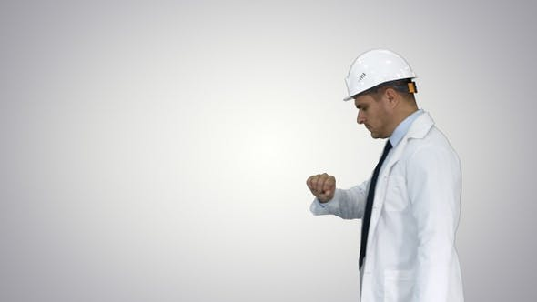 Thumbnail for Portrait of architect wearing hardhat looking at watch