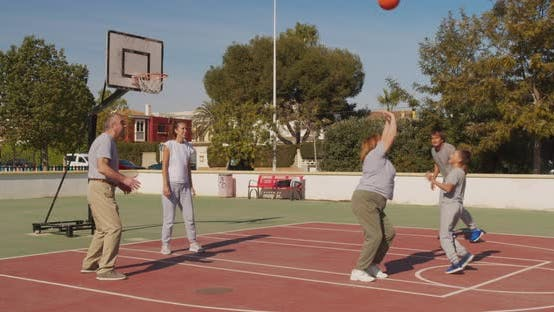 Multigeneration Family Playing Basketball on Outdoor Court