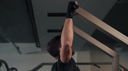 Der männliche Athlet zieht sich auf die horizontale Leiste, Seitenansicht